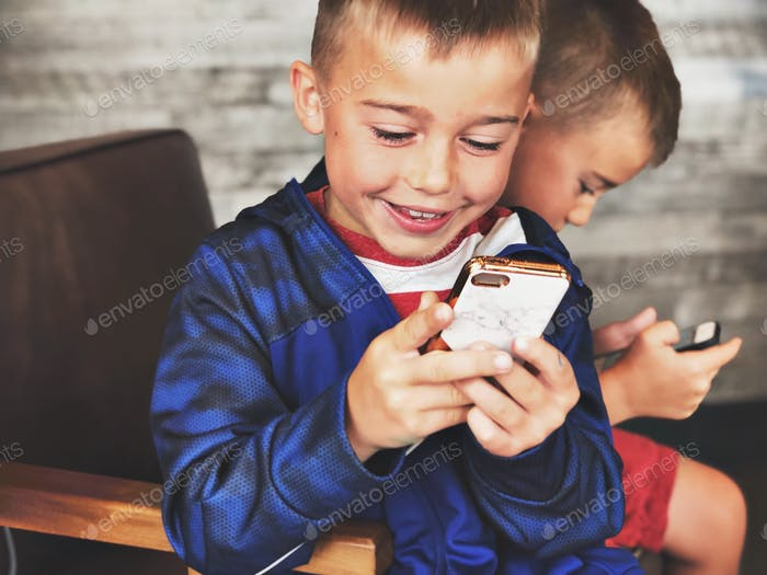 Boys playing on devices smiling looking at device