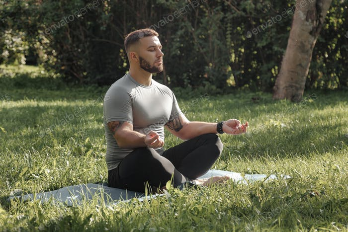 Millennial athletic man meditates outdoor in park, doing yoga. Concept of relaxation and meditation