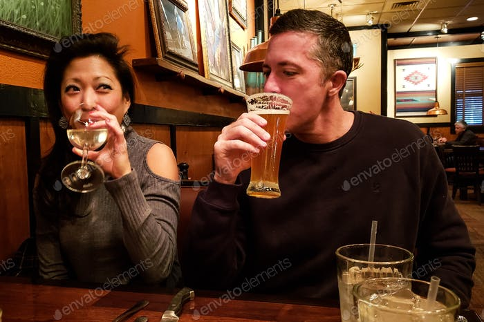Millenial couple on a date at happy hour having beer and wine with a twinkle in their eye....