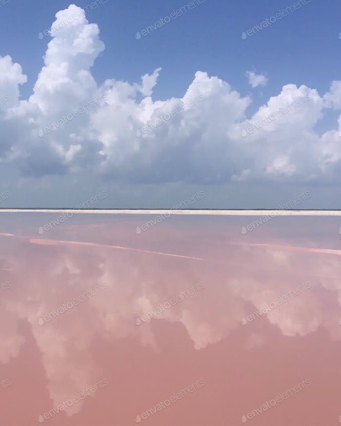 Beautiful fluffy clouds on blue skies over pink lagoon in Las Coloradas, Yucatán, Mexico.