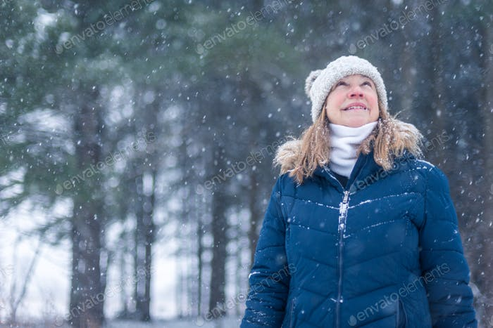 Woman outdoors looking up at snow falling in woods