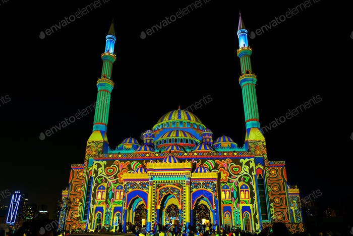 A mosque in Sharjah lit up with bright and colourful light display at night