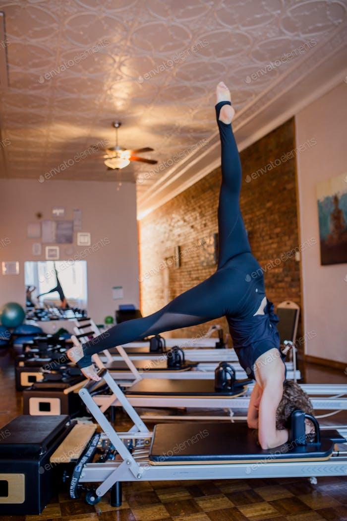 Woman exercising on Pilates Reformer machine.