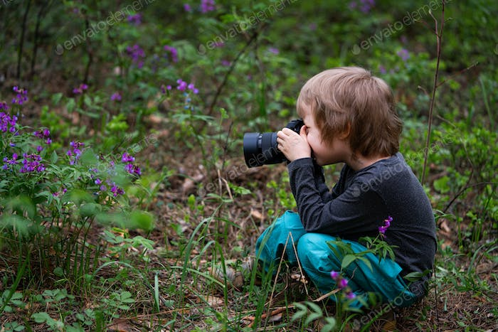 Little Boy using digital camera taking photo in the summer forest, hobbies concept