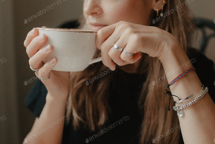 Hands hold a cup of coffee close-up