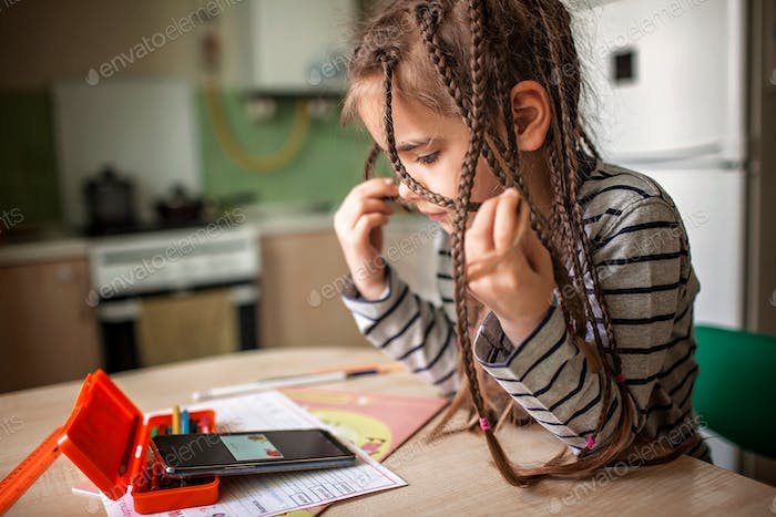 Pretty stylish schoolgirl studying math during her online lesson at home, self-isolation pupil, life