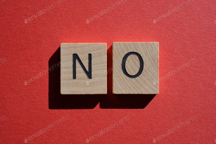 No, word in 3D wooden alphabet letters on a bright red background with copy space