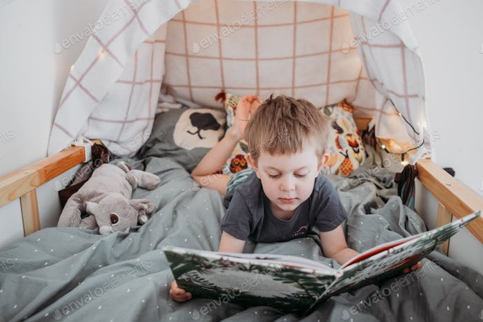 little boy reading book in his bed at home. spending time at home during lockdown. self isolation,