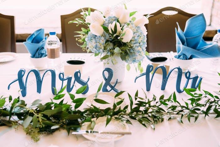 """"""" Mrs. & Mr."""" -Schild als Tischdekoration, neben einem Strauß hübscher Blumen"""