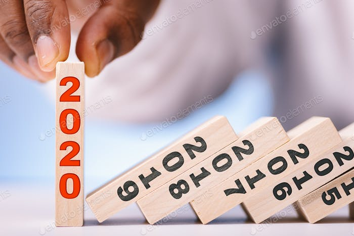 African American man holding a blockchain that says 2020 while other blocks fall with years prior