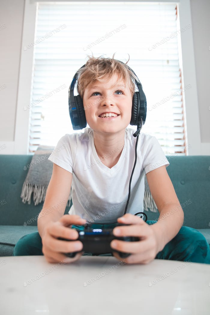 Boy on couch playing video games with a headset and controller in a brightly lit living room