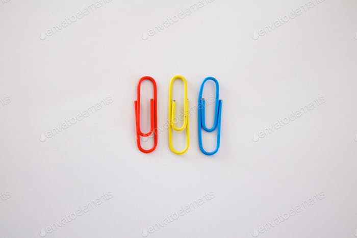 Red yellow and blue paper clips on white background primary colors flat lay