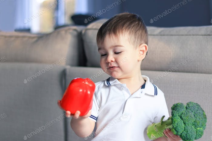 Cute happy smiling little boy looking at red pepper holding raw vegetables in his hands