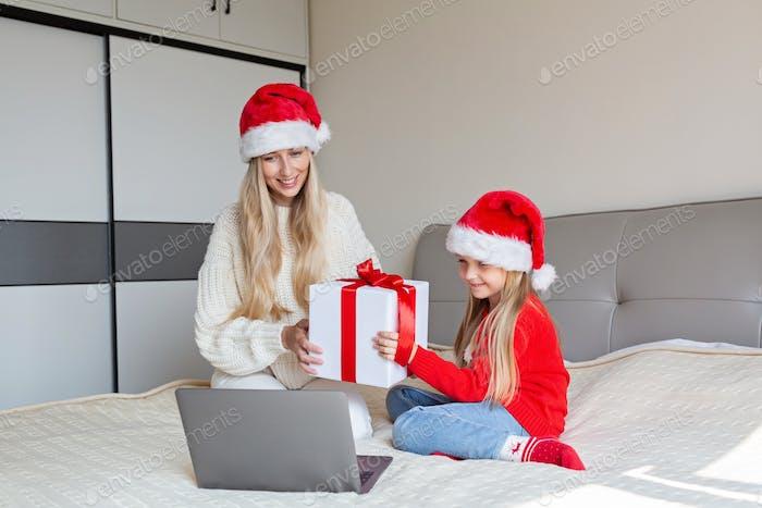 Mutter und Kind rufen Oma und Opa zu Online-Glückwünschen zu Weihnachten an. Video chat
