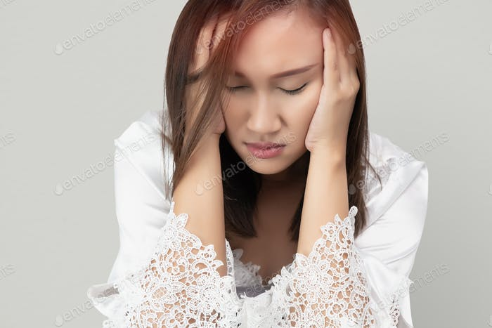 Asian woman in lace nightgown and white satin robes has a headache, isolated on gray background