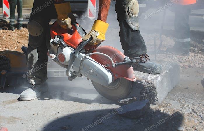 Bauarbeiter mit Trennmaschine Elektrowerkzeug Betonbruch auf der Straßenbaustelle
