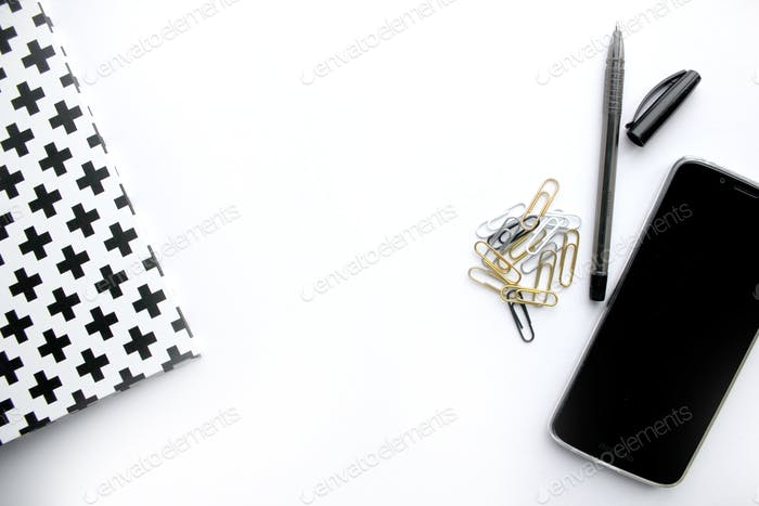 Desktop items flat lay style - binder, paper clips, cell phone, pen