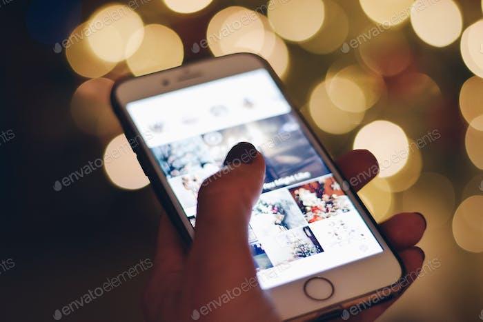 Teléfono móvil con imágenes de redes sociales de Instagram en la pantalla y luces bokeh en el fondo