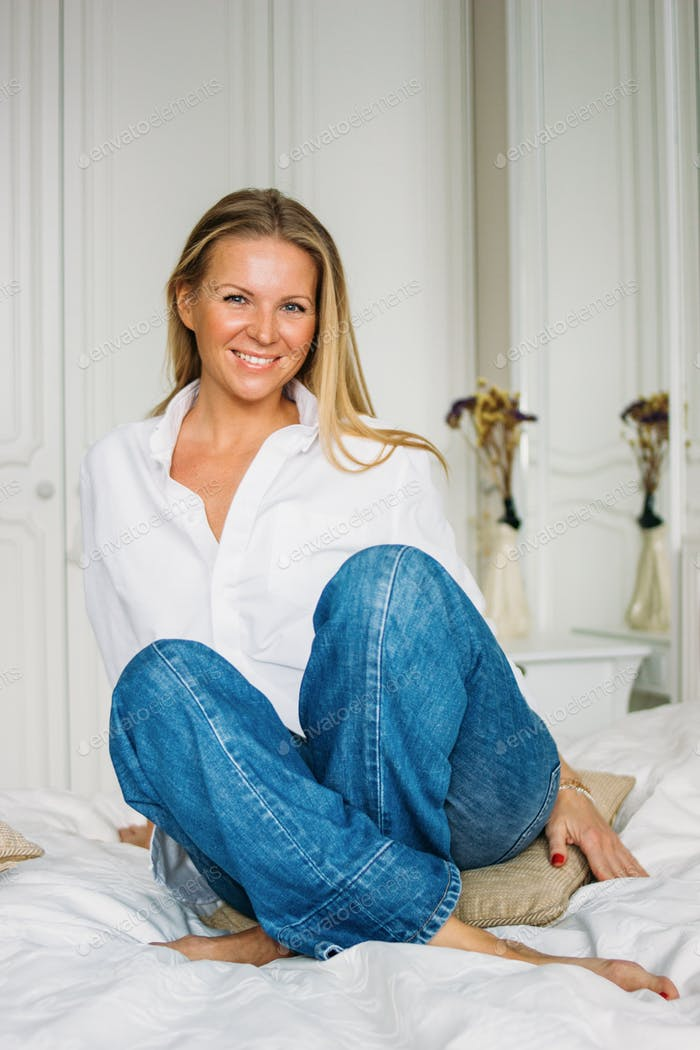 Friendly charming blonde woman with long fair hair in casual clothing sitting on the bed in bright