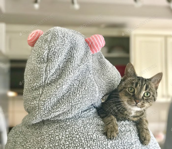 A woman carries her cat over her shoulder while wearing a mouse robe with ears in the kitchen