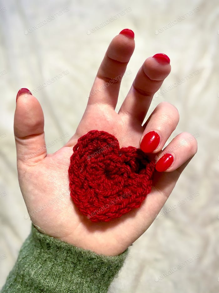 A hand with a red crochet heart in the palm