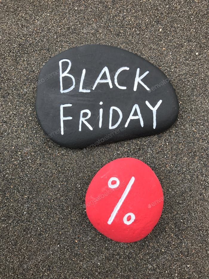 Black Friday text graved over two stones over volcanic sand
