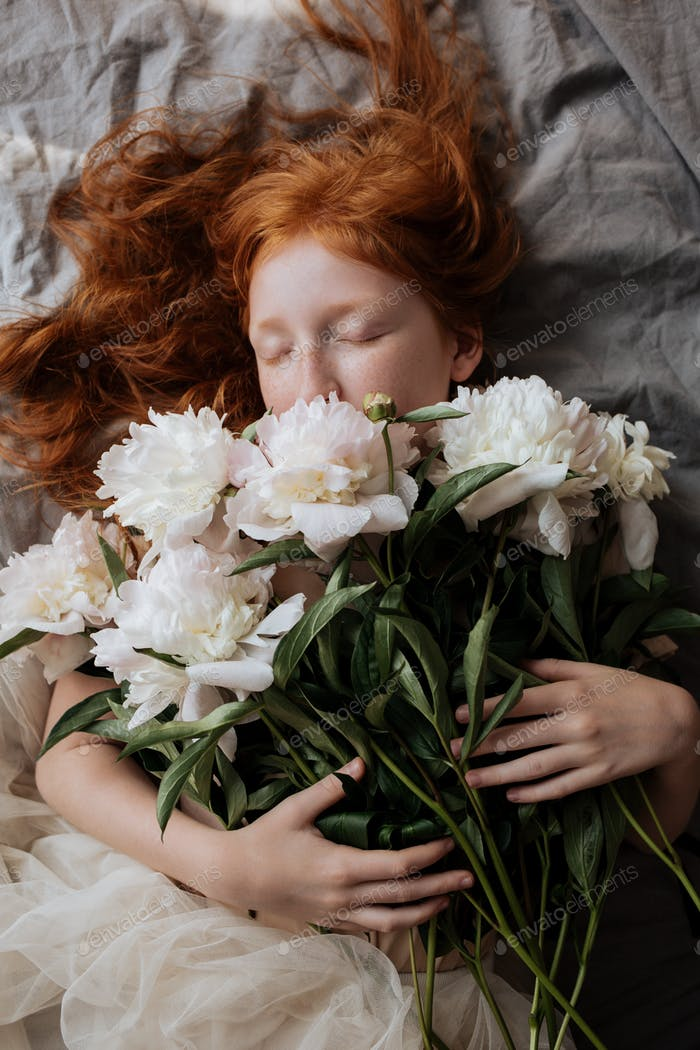 Red-haired beautiful girl embraces a bunch of pink peonies while lying on the bed.