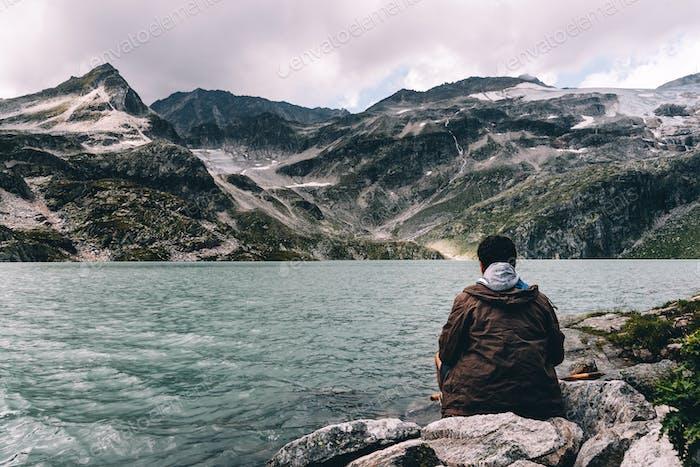 Adult middle aged man sitting at Alpine lake