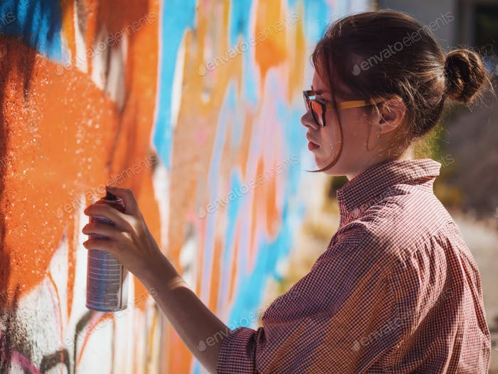 Girl drawing graffiti art on street wall