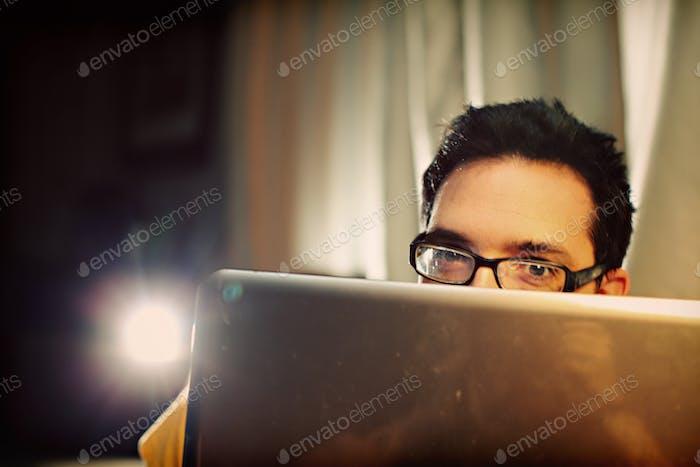 Hombre mirando por encima de una computadora portátil