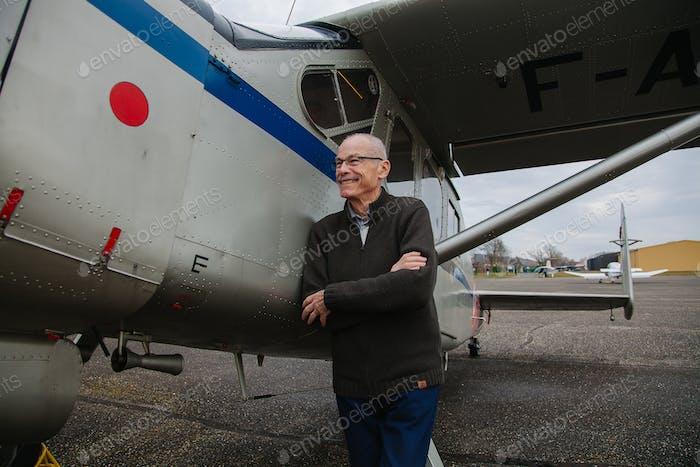 Hombre mayor posando con un viejo avión