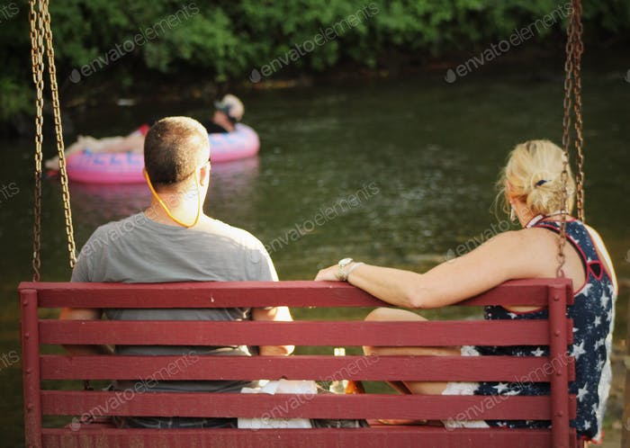 Couple having moment together on a swing at riverfront