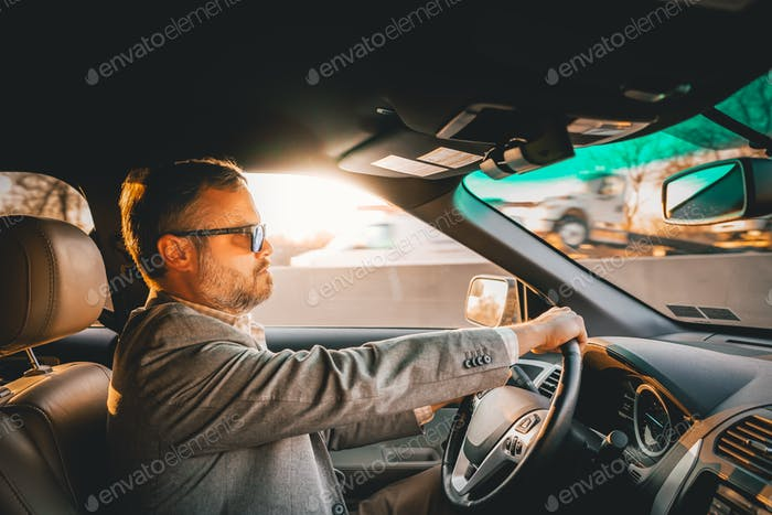 Man driving car commuting to work