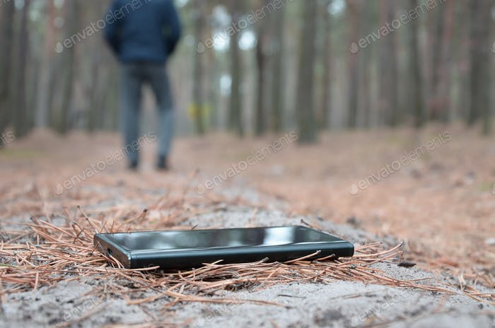 Young man loses his smartphone on Russian autumn fir wood path.
