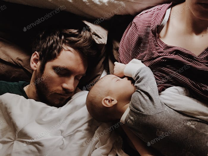 husband and baby fast asleep on mama
