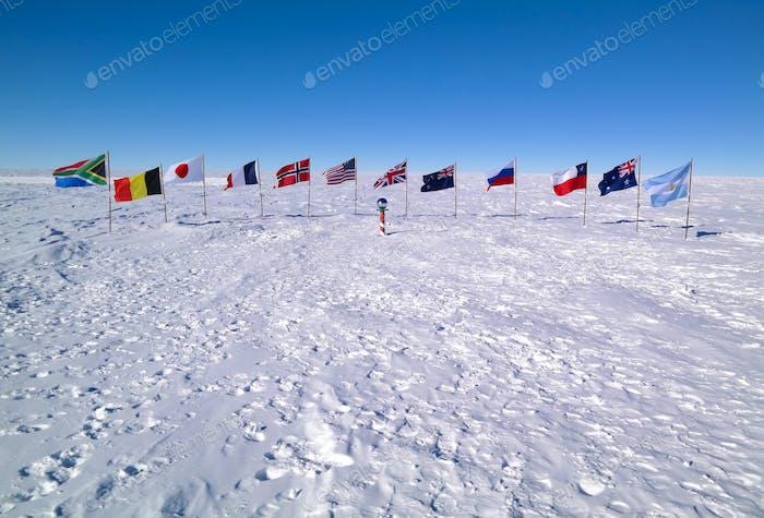 Zwölf Flaggen in den weißen sastrugi Schnee um die zeremonielle Südpol-Marker, die