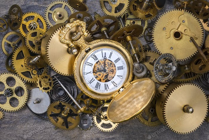 Pocket watch and a selection of dusty old brass clock parts.