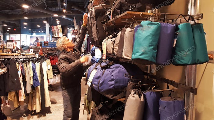 A man reaching for an item in the outdoor hiking section of a retail store. Retail Shopping. Senior