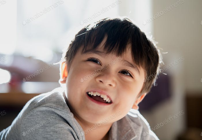 Happy kid looking up with smiling face, Healthy child relaxing at home,Boy having fun in living room