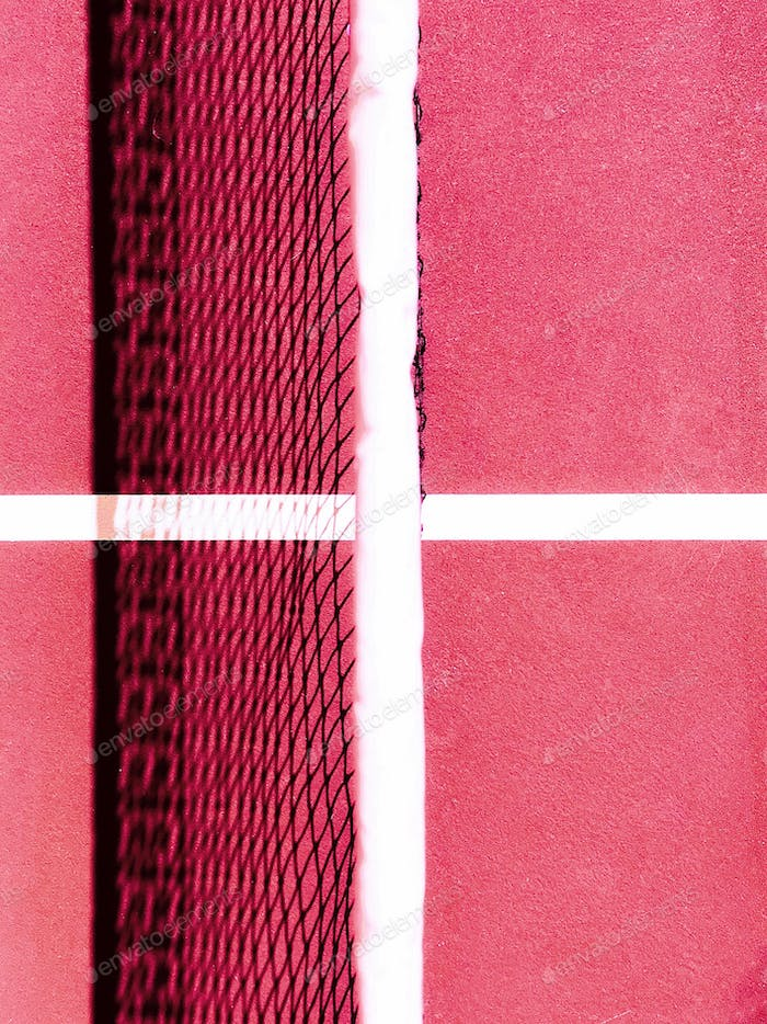 Looking straight down at the dividing net on a pink textured tennis court with strong shadow from