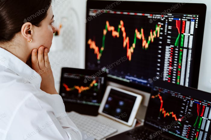 Young female cryptocurrency trader sitting at desk looking at multiple screens monitoring stock
